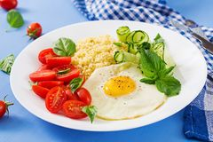 Millet porridge and tomato, cucumber salad and fried eggs. Healthy breakfast. Dietary menu. Millet porridge and tomato, cucumber salad and fried eggs royalty free stock photography