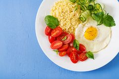 Millet porridge and tomato, cucumber salad and fried eggs. Healthy breakfast. Dietary menu. Millet porridge and tomato, cucumber salad and fried eggs. Top view royalty free stock photos