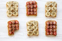 Healthy breakfast, dieting concept. Vegan toasts and one bitten toast with fruits, seeds, peanut butter on white wooden background royalty free stock photo