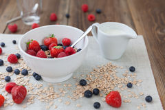 Healthy breakfast. Different berries and muesli on a wooden table Royalty Free Stock Photo