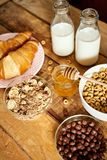 Healthy breakfast with different types of breakfast cereal with a spoon, honey croissants and milk. Healthy morning breakfast with different types of breakfast royalty free stock images