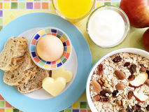 Healthy breakfast with egg, bread, cheese, yoghurt and cereals. Healthy breakfast with oat flakes, raisins, almonds, nuts, dried apples, egg, wholemeal bread Royalty Free Stock Images