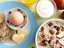 Healthy breakfast with egg, bread, cheese, yoghurt and cereals. Healthy breakfast with oat flakes, raisins, nuts, almonds, dried apples, egg, wholemeal bread Royalty Free Stock Photography