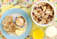Healthy breakfast with egg, bread, cheese, yoghurt and cereals. Healthy breakfast with oat flakes, raisins, nuts, almonds, dried apples, egg, wholemeal bread Stock Photo