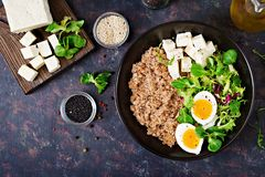 Healthy breakfast with egg, cheese, lettuce and buckwheat porridge on dark background. Proper nutrition. Dietary menu. Flat lay. Top view stock photography