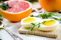 Healthy breakfast with eggs, grapefruit and fresh arugula Stock Images