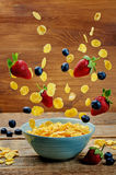 Healthy breakfast with flying corn flakes, strawberries and blue Stock Images