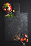 Healthy breakfast food frame. Chia pudding with fresh berries and mint on black slate stone board over dark background. Top view, copy space Royalty Free Stock Images
