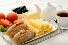 Healthy breakfast - fresh buns, cheese, tomato and olives. Stock Photo
