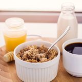 Healthy breakfast fresh cereal, milk bottle, coffee cup and honey ja. R, toned warm sunny morning light royalty free stock photography