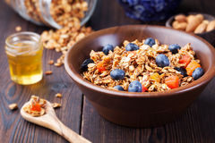 Healthy breakfast. Fresh granola, muesli with berries, honey and milk in a wooden bowl Top view Stock Images