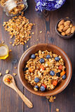 Healthy breakfast. Fresh granola, muesli with berries, honey and milk in a wooden bowl Top view Royalty Free Stock Photography