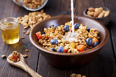Healthy breakfast. Fresh granola, muesli with berries, honey and milk Royalty Free Stock Photos