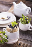 Healthy breakfast. Fresh homemade mug cake with forest blueberries in a white ceramic bowl sprig of ripe berries on the Stock Photos