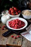 Healthy breakfast is fresh organic raspberries, strawberries with oat flakes and milk on an old wooden background. Rustic style. Food Stock Photography
