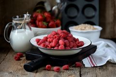 Healthy breakfast is fresh organic raspberries, strawberries with oat flakes and milk on an old wooden background. Rustic style. Food Royalty Free Stock Photo