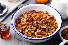 Healthy breakfast. Fresh pumpkin granola, muesli, pecan nuts, cranberries and maple syrup royalty free stock photography