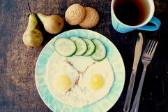 Healthy breakfast, fried eggs, cucumber, fruit, tea royalty free stock photos