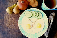 Healthy breakfast, fried eggs, cucumber, fruit, tea stock image