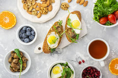 Healthy breakfast with fried eggs, fresh bread, salad, berries, tomatoes, nuts, beverage cup, arugula,  mushrooms on a Royalty Free Stock Photo
