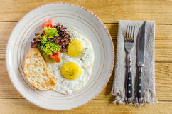 Healthy breakfast: Fried eggs, tomatoes, herbs and bread, with cutlery, on a wooden table. View from above Stock Image
