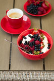 Healthy breakfast on garden furniture: cottage cheese with sour cream, strawberry, raspberry and blueberry, espresso. And plate of fresh ripe berries on wooden Royalty Free Stock Photography