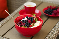 Healthy breakfast on garden furniture: cottage cheese with sour cream, strawberry, raspberry and blueberry, espresso. And plate of fresh ripe berries on wooden Royalty Free Stock Image