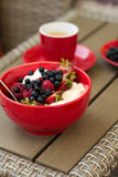 Healthy breakfast on garden furniture: cottage cheese with sour cream, strawberry, raspberry and blueberry, espresso. And plate of fresh ripe berries on wooden Royalty Free Stock Photos