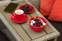 Healthy breakfast on garden furniture: cottage cheese with sour cream, strawberry, raspberry and blueberry, espresso. And plate of fresh ripe berries on wooden Stock Photography