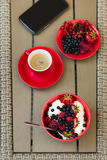 Healthy breakfast on garden furniture: cottage cheese with sour cream, strawberry, raspberry and blueberry, espresso. And plate of fresh ripe berries on wooden Royalty Free Stock Photo