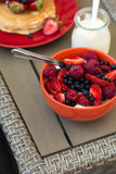 Healthy breakfast on garden furniture: cottage cheese with sour cream, strawberry, raspberry and blueberry, pancakes, yogurt Stock Image