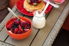 Healthy breakfast on garden furniture: cottage cheese with sour cream, strawberry, raspberry and blueberry, pancakes, yogurt Stock Photography