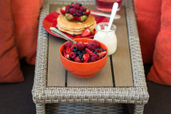Healthy breakfast on garden furniture: cottage cheese with sour cream, strawberry, raspberry and blueberry, pancakes, yogurt Stock Photo