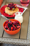 Healthy breakfast on garden furniture: cottage cheese with sour cream, strawberry, raspberry and blueberry, pancakes, yogurt Stock Images