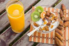 Healthy breakfast. A glass of fresh orange juice and a dish of yogourt with fruits royalty free stock image