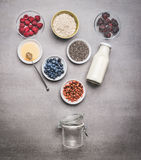 Healthy breakfast glass jar making with ingredients: chia seeds, goji berries, oatmeal , fresh berries , honey and milk or yogurt Royalty Free Stock Photography