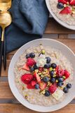 Healthy breakfast goals. Cooked oatmeal with seasonal berries, nuts and edible flowers. Nutritional meal. Organic food.