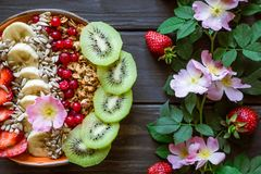 Granola with fruit and pink flowers royalty free stock image
