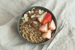 Healthy breakfast. Granola with milk, strawberry and nuts in grey ceramic bowl. Diet food concept stock images