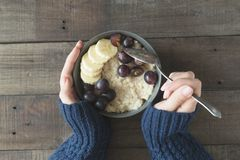 Healthy breakfast. Grey bowl with oatmeal porridge and fruits in women`s hands. Diet food concept.  Stock Photos