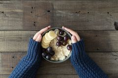 Healthy breakfast. Grey bowl with oatmeal porridge and fruits in women`s hands. Diet food concept.  Royalty Free Stock Photo