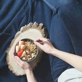 Healthy breakfast. Grey ceramic bowl with granola, strawberry and nuts in woman`s hands. Diet and vegetarian food concept.  Royalty Free Stock Photos