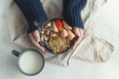 Healthy breakfast. Grey ceramic bowl with granola, strawberry and nuts in woman`s hands. Diet and vegetarian food concept stock image