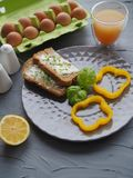 Healthy breakfast with home made bread and eggs and orange juice on grey plate and grey background ideal for culinary blogger or c stock photography