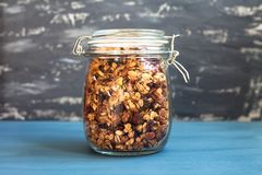Healthy breakfast of homemade muesli in a glass jar on a gray background royalty free stock photos