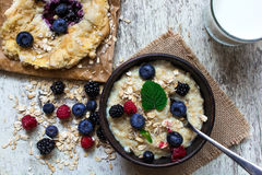 Healthy breakfast. homemade oatmeal with berries, blueberry cake and glass of milk. top view Royalty Free Stock Image