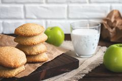 Daily healthy breakfast. Homemade oatmeal cookies, milk, fruit on dark background royalty free stock photo