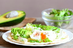 Healthy breakfast idea. Delicious tortilla with a poached egg, avocado slices, napa cabbage, salad mix, sauce and spices Royalty Free Stock Photos