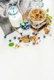 Healthy breakfast ingrediens. Homemade granola in open glass jar, milk or yogurt bottle, blueberries and mint Royalty Free Stock Photography