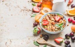 Healthy breakfast ingredients. Bowl of oat granola with milk, fresh fruit, berries and honey Stock Photo